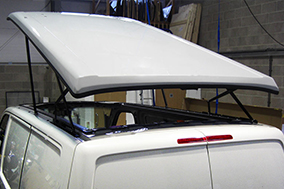 Roof attached with rear scissor hinges and front hydraulic rams.